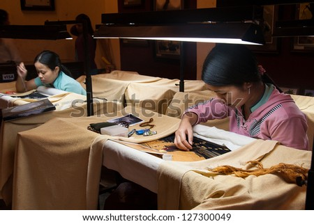 HOI AN, VIETNAM - JANUARY 9: Two unidentified women work on traditional embroideries  on January 9, 2008 in Hoi An, Vietnam. Embroidery has been a traditional handicraft of Vietnam over 700 years.