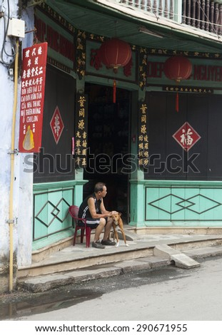 Hoi An, Vietnam - Jun 20, 2015: Unidentified old man sitting in front of his ancient house with his dog laying beside in Hoi An town, Quang Nam province. Hoi An is a World Heritage Site by UNESCO.
