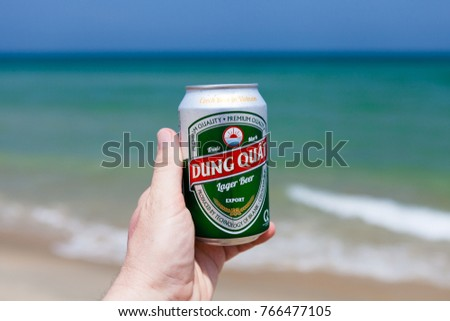 Hoi An, Vietnam - march 15 2017: hand holding can of cold Dung Quat beer against emerald ocean and blue sky