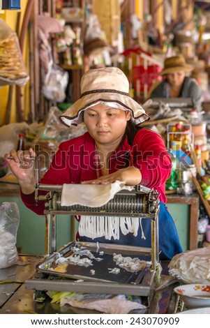 HOI AN, VIETNAM - MARCH 31: Unidentified woman making rice noodles on the Hoi An market, Vietnam on March 31, 2014. - stock photo