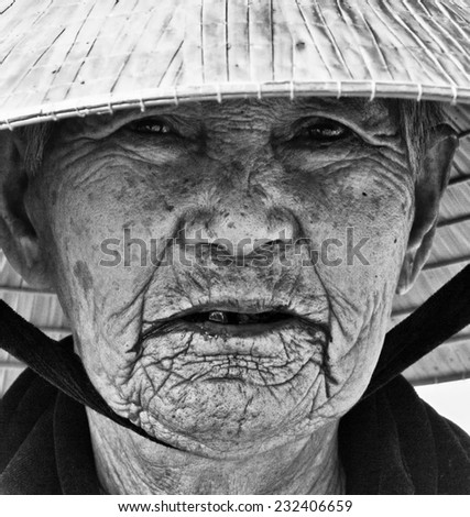 Hoi An, Vietnam - November 11 2014: Very Old Vietnamese Woman Working Near River in Hoi An a City Near Da Nang Vietnam  - stock photo