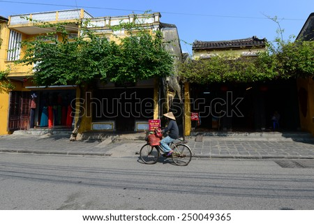 HOIAN, VIETNAM, JANUARY 23: A woman ride bicycle in Hoian ancient town on January 23, 2015 in Hoian, Vietnam. Hoian is recognized as a World Heritage Site by UNESCO. - stock photo