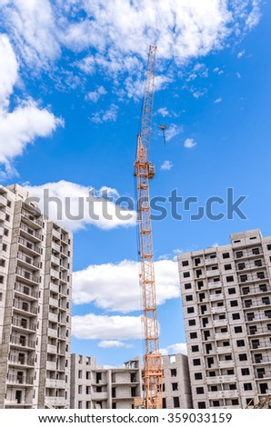 Hoist crane and multistory building - stock photo