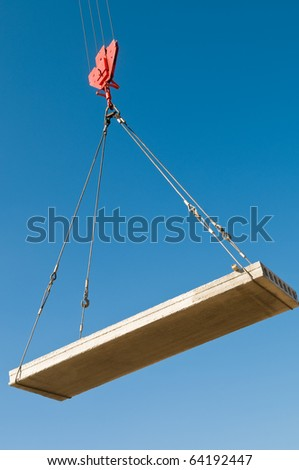 hoisting a concrete slab with crane using metal slings - stock photo