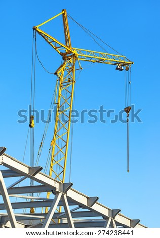 hoisting crane against the blue sky - stock photo