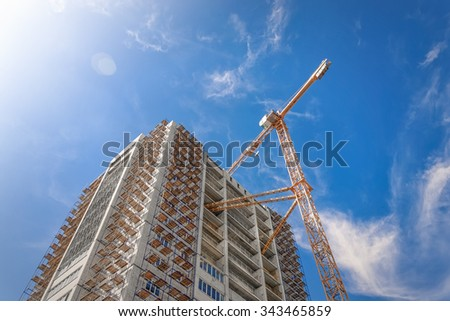 Hoisting crane and house construction - stock photo