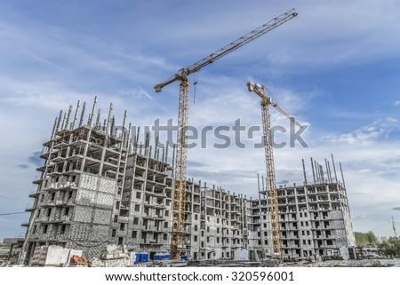 Hoisting crane and new multi-storey building - stock photo