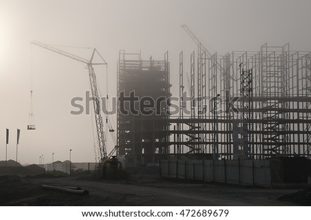 Hoisting crane and unfinished building in dense fog early in the morning look like silhouettes
