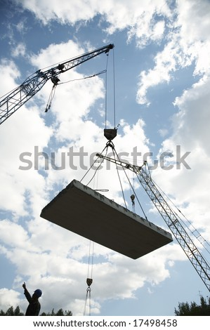 Hoisting crane lifts heavy concrete grey slab