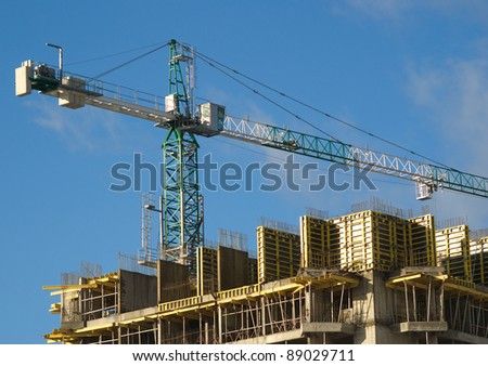 Hoisting tower crane above building house