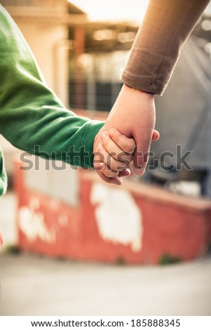Hold my hand - Mother and son holding hands - stock photo