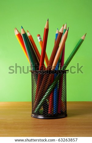 holder basket full of colored pencils on green background - stock photo