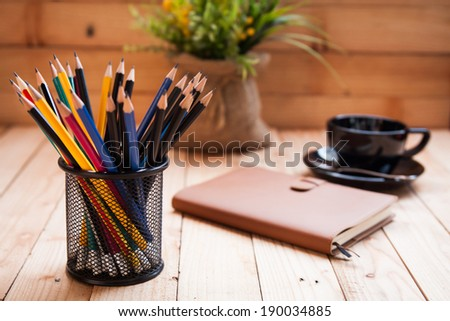 holder basket full of pencils with notebook and coffee cup - stock photo