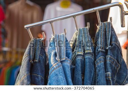 Holder belt of jeans on hanger in market - stock photo