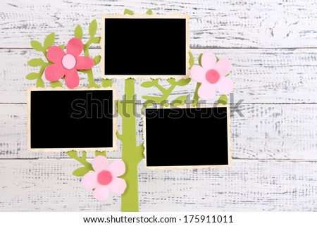 Holder in form of tree with instant photo cards on color wooden background