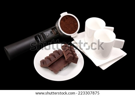 Holder of an espresso machine with ground coffee, two cups and saucers and a plate with chocolate pieces on a black background