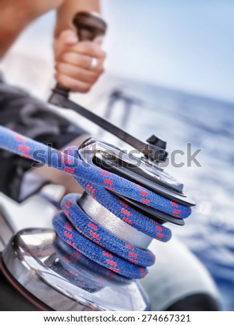 Holder of rope on sailboat, man pulling handle of spool, macro photo of yacht detail, working on water transport, luxury summer time sport  - stock photo