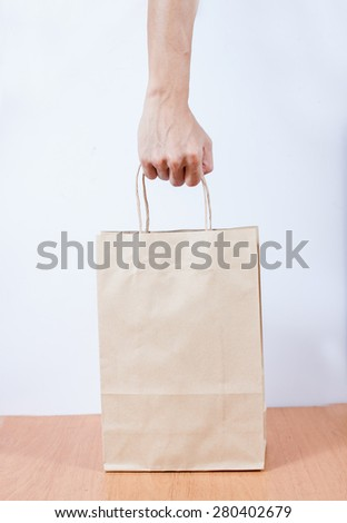 holding a brown paper bag with contents in his hand - stock photo