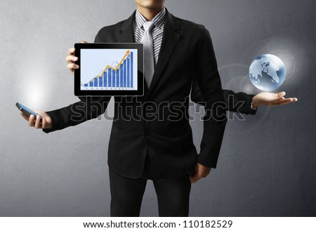holding a glowing earth and tablet,mobile phone in his hands - stock photo