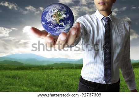 holding a glowing earth globe in his hand - stock photo