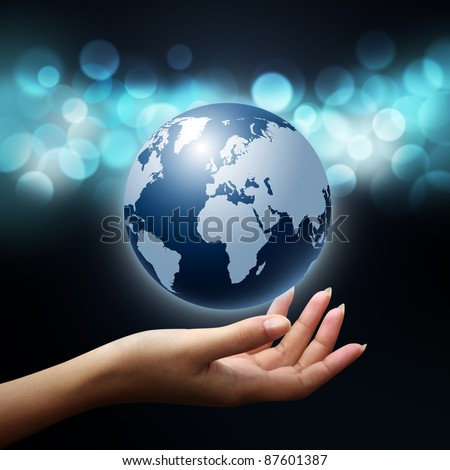 holding a glowing earth globe in woman hands on blue background - stock photo
