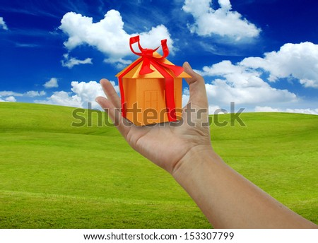 holding a Golden Home with lanscape - stock photo