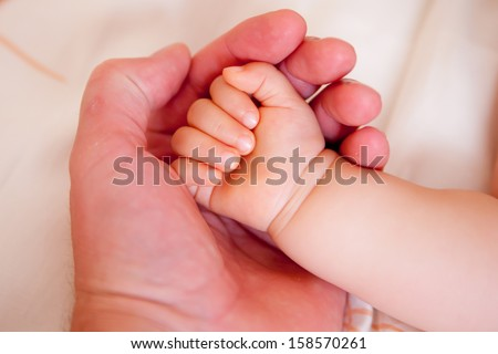 holding a hand of the newborn child - stock photo