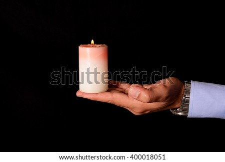 Holding a Light candle on black background