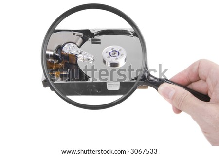 Holding a magnifying glass over a hard drive - stock photo