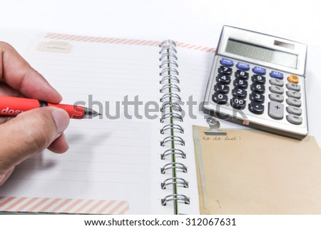 holding a red pen writing on notebook - stock photo