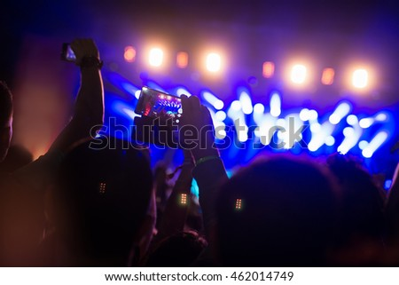 Holding a smart phone at a concert and recording.