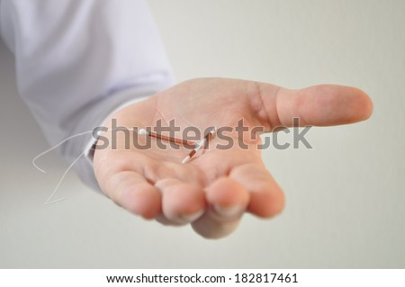 Holding an IUD birth control copper coil device in hand, used for contraception - front view - stock photo