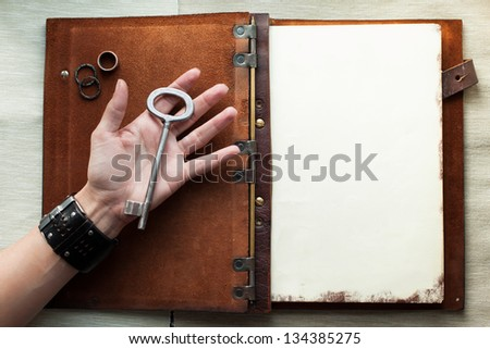 Holding an old key over a book - stock photo