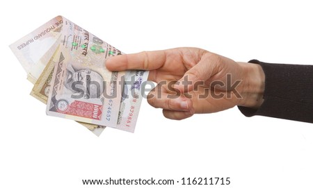 Holding and giving Indian rupees to someone - stock photo