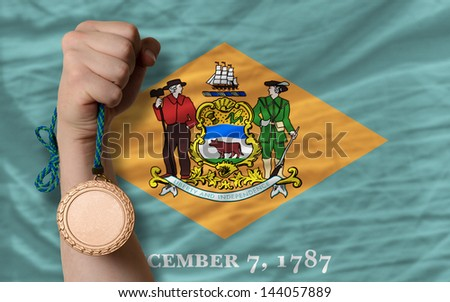 Holding bronze medal for sport and flag of us state of delaware - stock photo