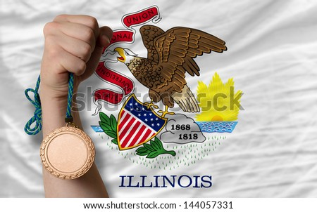 Holding bronze medal for sport and flag of us state of illinois - stock photo