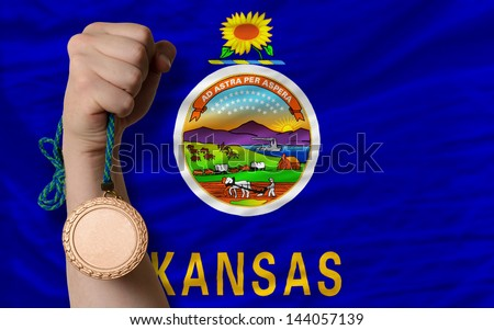 Holding bronze medal for sport and flag of us state of kansas - stock photo