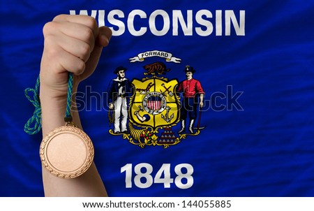 Holding bronze medal for sport and flag of us state of wisconsin - stock photo