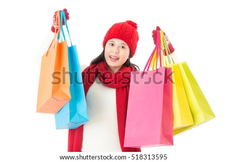 holding colorful shopping bags for christmas gifts buying. young beautiful asian woman isolated on white background.