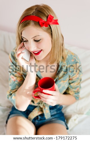 holding cup of hot drink & mobile cell phone beautiful blonde pinup young woman happy smiling girl with red lipstick - stock photo