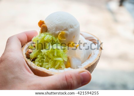 Holding delicious coconut ice cream in hand, close up - stock photo