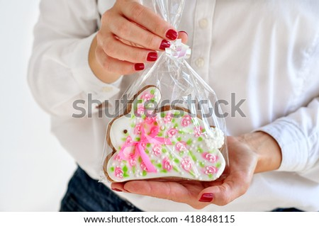 Holding Easter bunny gingerbread cookie - stock photo