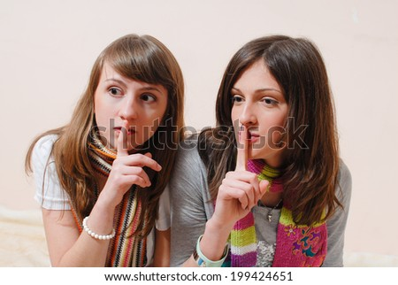 holding fingers on lips in silence sign 2 beautiful women girlfriends having fun together looking at camera copy space on light background closeup portrait picture  - stock photo