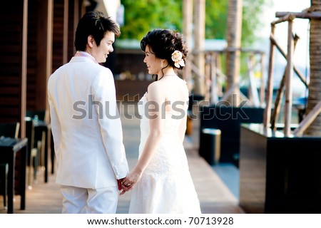 Holding hand to each other by groom and bride - stock photo
