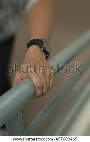 Holding handrail while using staircase for your safety