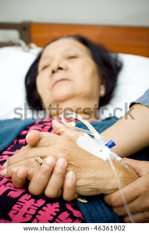 holding hands as for mental support to the sick people. grandma hand being hold by her daughter