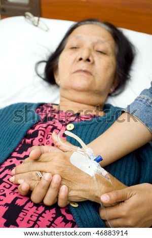 holding hands as for mental support to the sick people. grandma hand being hold by her daughter - stock photo