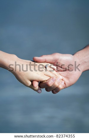 Holding hands at the beach - stock photo