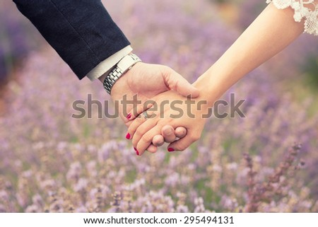 Holding hands. Close up of a male and female hands holding each other. Lavender field in the back. - stock photo