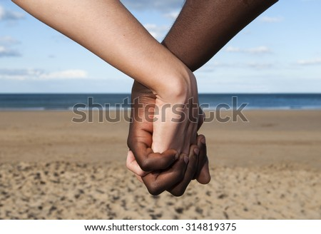 Holding hands couple close up  male female  multicultural sea and sand  together  love  peace symbol